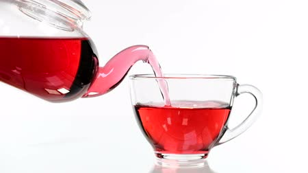 rozelle : red rose tea in a glass teapot and a cup on a white background. Stock Footage