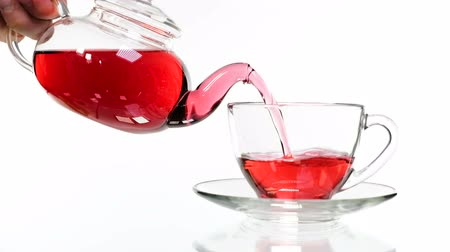 tonik : red rose tea in a glass teapot and a cup on a white background. Stok Video