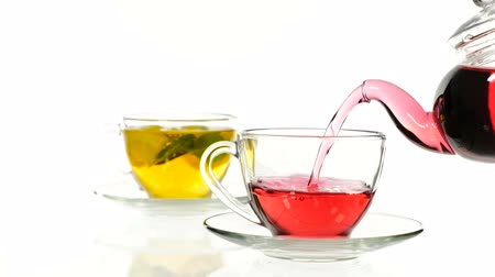 karkade : red rose tea in a glass teapot and two cup on a white background.