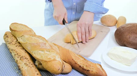 bagietka : Fresh bread slice and cutting knife on rustic table. With wooman hands