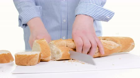 migalhas : Woman Hands Cutting Bread In Kitchen. Close Up Of Female Hands Holding Knife, Slicing White Baguette On Chopping Board. Cooking Home