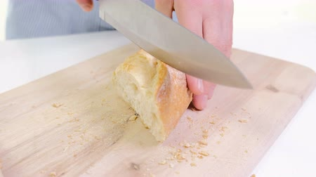 bagietka : Woman Hands Cutting Bread In Kitchen. Close Up Of Female Hands Holding Knife, Slicing White Baguette On Chopping Board. Cooking Home