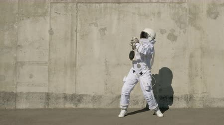 base station : funny astronaut makes dancing. Against a background of a concrete wall. Stock Footage