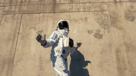 conquérir : funny astronaut makes dancing. Against a background of a concrete wall. Vidéos Libres De Droits