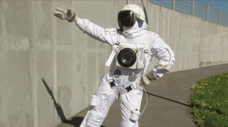 base station : funny astronaut makes dancing. Against a background of a concrete wall. 4K