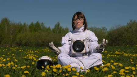косплей : Girl cosmonaut practicing meditation on a flower field