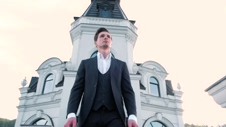 kijárat : Portrait of a handsome businessman standing outdoors near white building