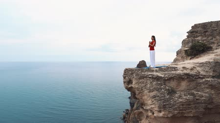 skalní útes : Woman standing and meditating on a cliff over the ocean. Yoga on the cliff. Dostupné videozáznamy