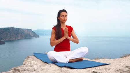 armoni : girl sitting on rock by sea, meditating in lotus yoga pose, concentrating, relaxing mind, soul and body.