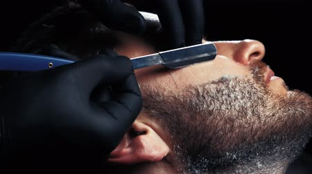 barbering : Close-up of hands in black gloves shaving the face of a man