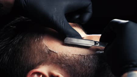 barbering : Close up of a handsome man getting his beard shaved in a hairdresser professional hairdresser using a razor shaving his customer profession. Stock Footage