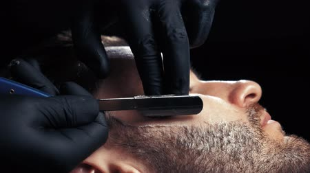 veszélyes : Close up of a handsome man getting his beard shaved in a hairdresser professional hairdresser using a razor shaving his customer profession. Stock mozgókép