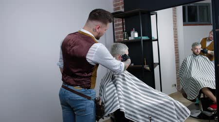 Tattoed barber makes haircut for customer at the barber shop by using hairclipper, mans haircut and shaving at the hairdresser, barber shop and shaving salon.