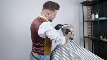 Making haircut. Young bearded man getting haircut by barber while sitting in chair at barbershop.