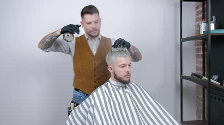 barbering : A professional baber working a hairstyle combing it with water. male client with blond hair.