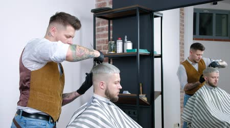 close cropped : A young guy gets a haircut with hair scissors with a comb. Stock Footage