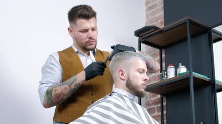 A young guy gets a haircut with hair scissors with a comb. Dostupné videozáznamy