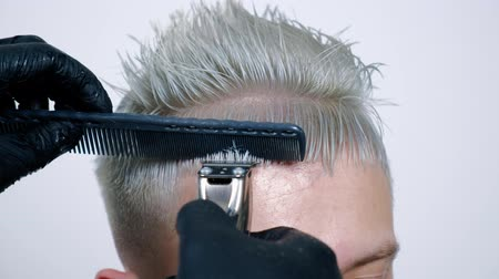 Male haircut with electric razor. Close up of man hair cut. Male hands barber shaving man with electric razor in barbershop. Barber cutting hair with hair trimmer