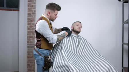 trimmelés : Shaving of beard. Barber cutting mens face hair with beard trimmer at barbershop. Stock mozgókép