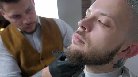kartáč na vlasy : Shaving of beard. Barber cutting mens face hair with beard trimmer at barbershop. Dostupné videozáznamy