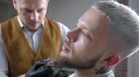 Shaving of beard. Barber cutting mens face hair with beard trimmer at barbershop. Dostupné videozáznamy