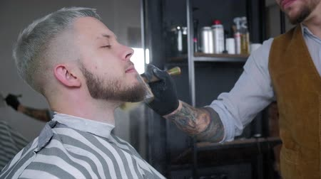 Barber sips talc on a brush. The video has a brown tint.