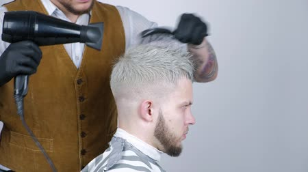 haardroger : Man kapsel in de salon. Mensenhaar het drogen in kapperswinkel. Kapper styling haar met föhn. Kappers afmaken. Haardroger man in de kapsalon Stockvideo