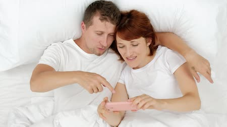 Couple Of Spouses Are Lying In Bed And Watching Smartphones - Communicates In Social Networks And Writes Messages Lying In Bed Before Going To Bed.