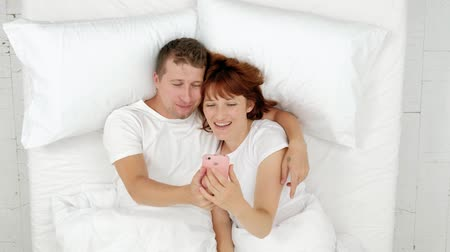 Top view on the young attractive couple lying in the bed and taking nice selfies on the smartphone. Dostupné videozáznamy