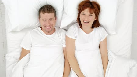 Top view of smiling couple having fun in bed hiding under blanket and looking into camera.
