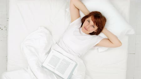 Happy girl reading a book in a white bed. top view