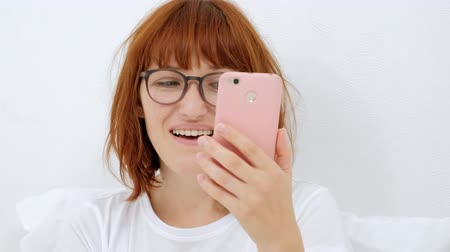 portrait of a girl with a phone, find your favorite tune in a smart phone smiling, listen to it through headphones, isolated on a white background.