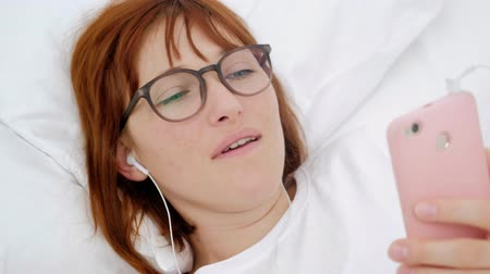 Top view portrait of pretty, attractive, brunette, charming, cheerful girl having fun using smart phone, headset on head, listening her favorite playlist, choosing, searching for song, lying on back.