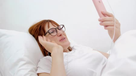Patient talking on mobile phone in bed. Young attractive woman in hospital bed. Connected world and mobile office concept.