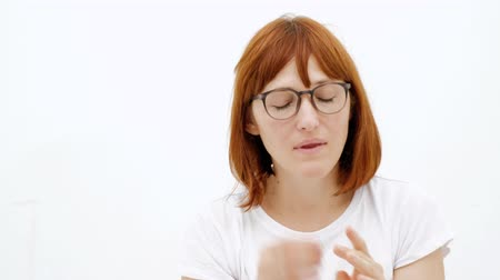 отменить : Woman putting ear plugs into her ears getting rid on noise in loud place. White background