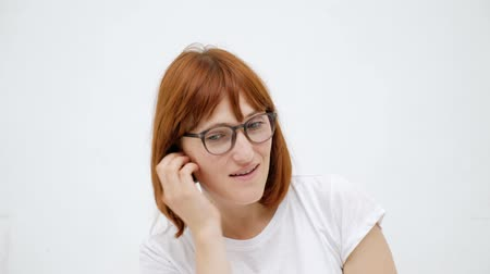 zrušit : Woman putting ear plugs into her ears getting rid on noise in loud place. White background