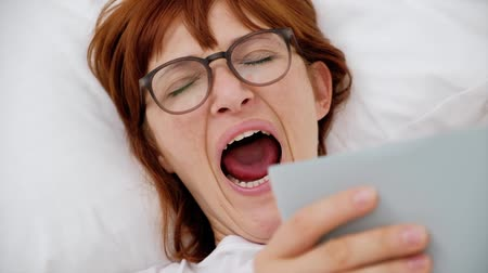 Girl yawning lying on the bed with a book. close up