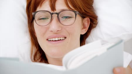 Red-haired girl reading a book in a white bed. top view