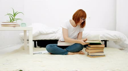 Pretty young woman sitting on her living room floor improvising using high stacks of books