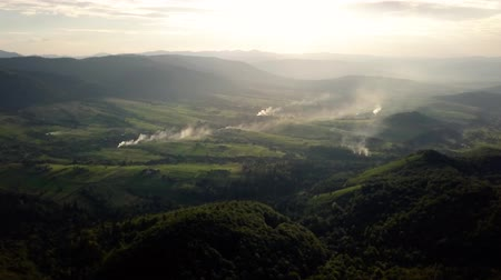 Aerial Drone Footage View: Flight over autumn mountain village with forests, fields and river in sunrise soft light.