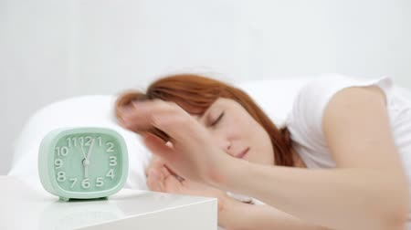 turning off : Wake up of an asleep girl stopping alarm clock on the bed in the morning. Stock Footage