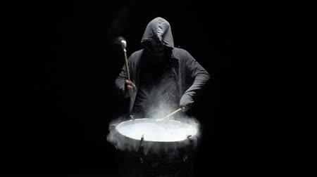 vurmalı : hooded man beats drum with flour Stok Video
