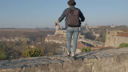 сумка : Man traveler with backpack explores the city looking at the panoramic view of the city and the coast. The concept of travel is discovering new places.