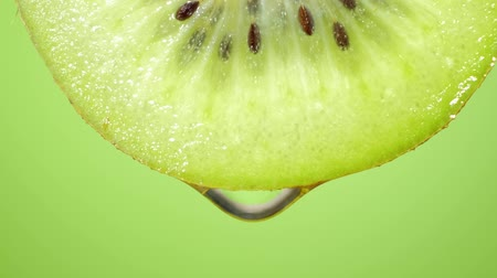 kivi : Close up or macro of a slice of kiwi, a drop of water falls in slow motion. Stok Video
