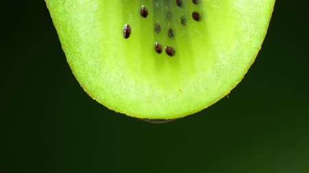 キウイ : Close up or macro of a slice of kiwi, a drop of water falls in slow motion. Black background