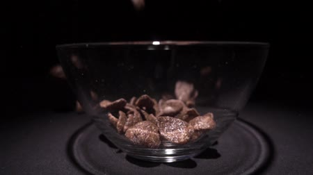 musli : Brown chocolate corn flakes fall in a plate with a pattern of flowers on the edge and are filled with milk. Closeup. Slow mo, slo mo, slow motion, high speed camera, Wideo