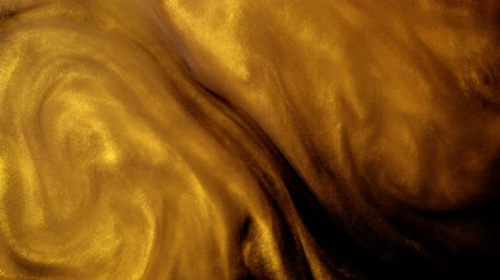pailettes : Golden ink or dust creating abstract cloud formations. Art backgrounds.