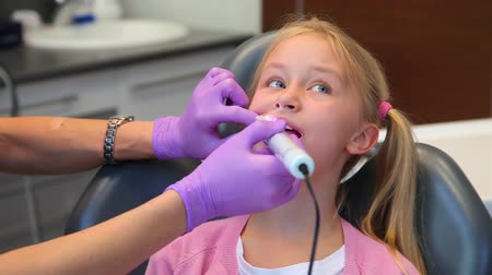 cadeira : Visit at dentist office, woman dentist treating teeth of little girl patient