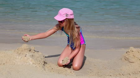 çocuk : Young girl in swimsuit builds a sand castle on the beach, summer vacation time