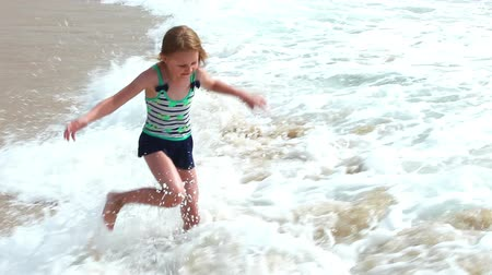 genç kız : Cute young girl having fun with sea waves on the beach, summer vacation time